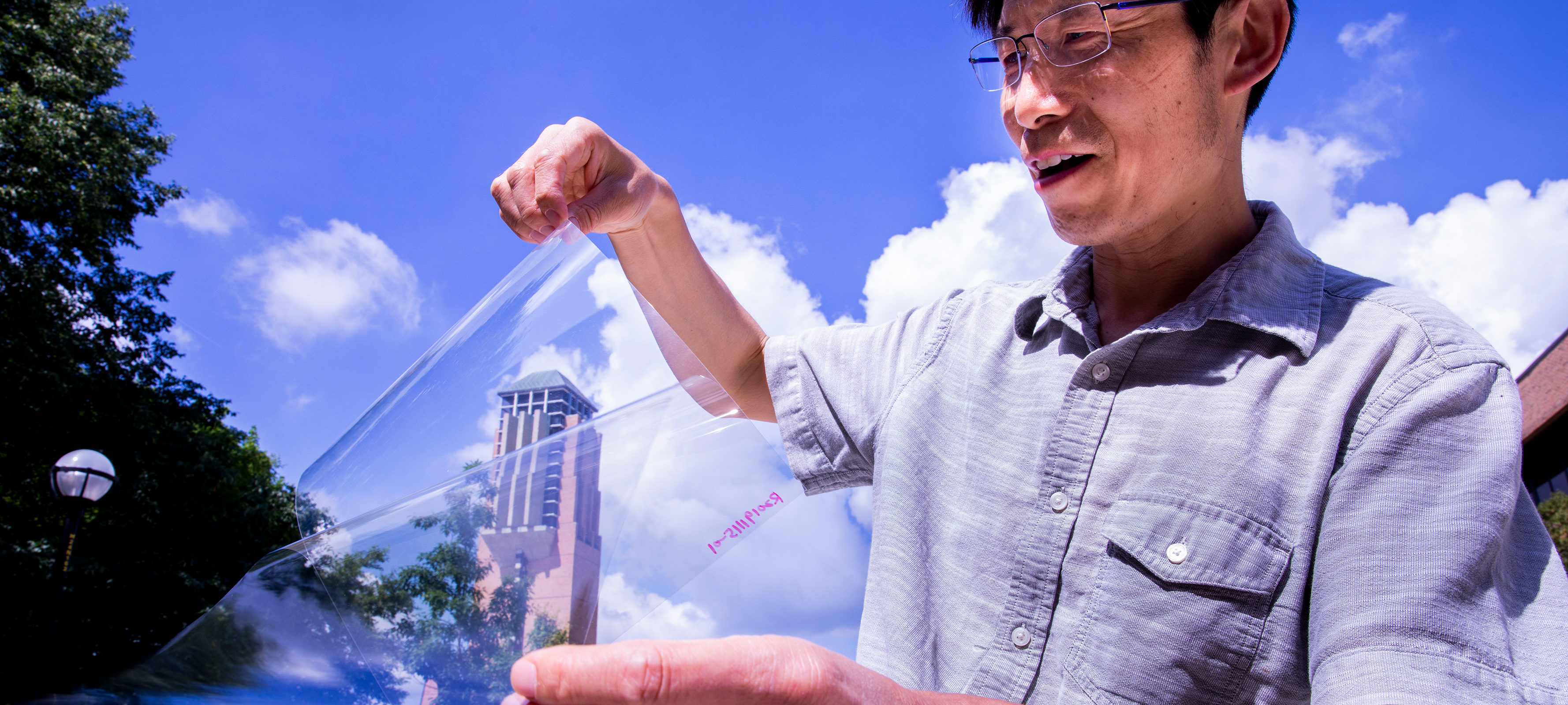 "Jay Guo holds a sheet of flexible transparent conductor on the University of Michigan's College of Engineering North Campus. The material sandwiches a thin layer of silver between two ""dielectric"" materials, aluminum oxide and zinc oxide, producing a conductive anti-reflection coating on the sheet of plastic."