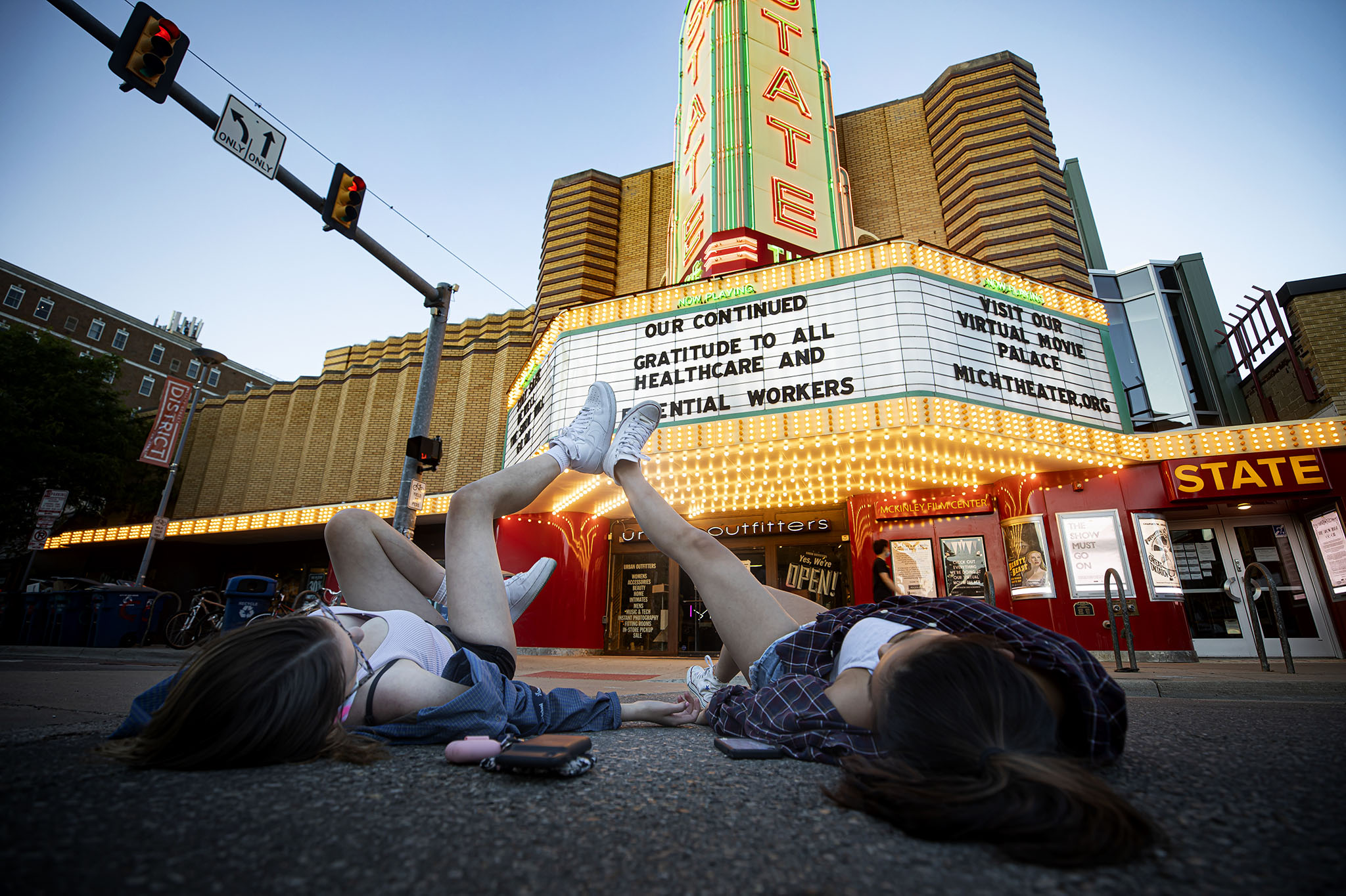 A photograph of two people laying on the ground outside of the State Theatre.