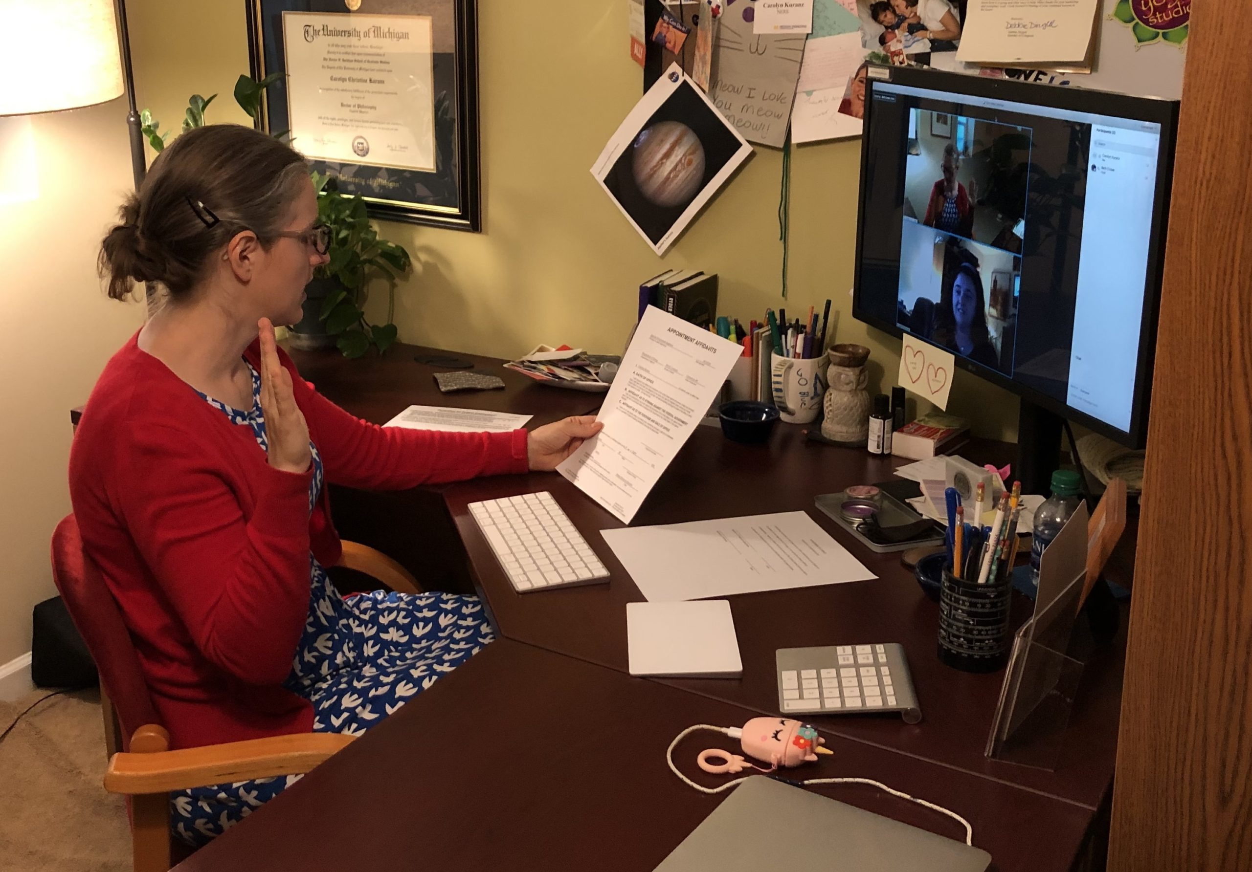 woman sits at computer desk while taking an oath in a virtual meeting and holding a piece of paper