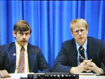 Two men in suits sitting in front of a blue curtain.