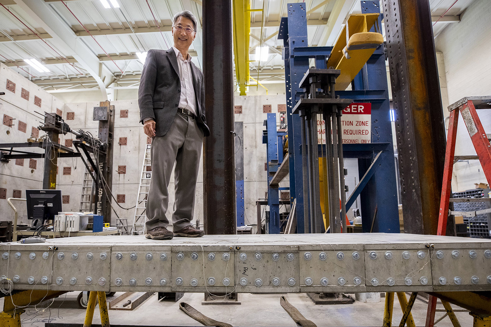 Professor Li stands atop a concrete bridge in a lab.