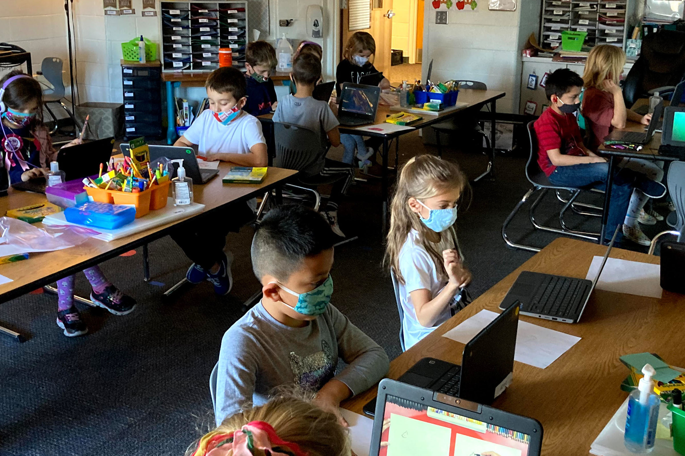 Kids learning in the classroom with laptops
