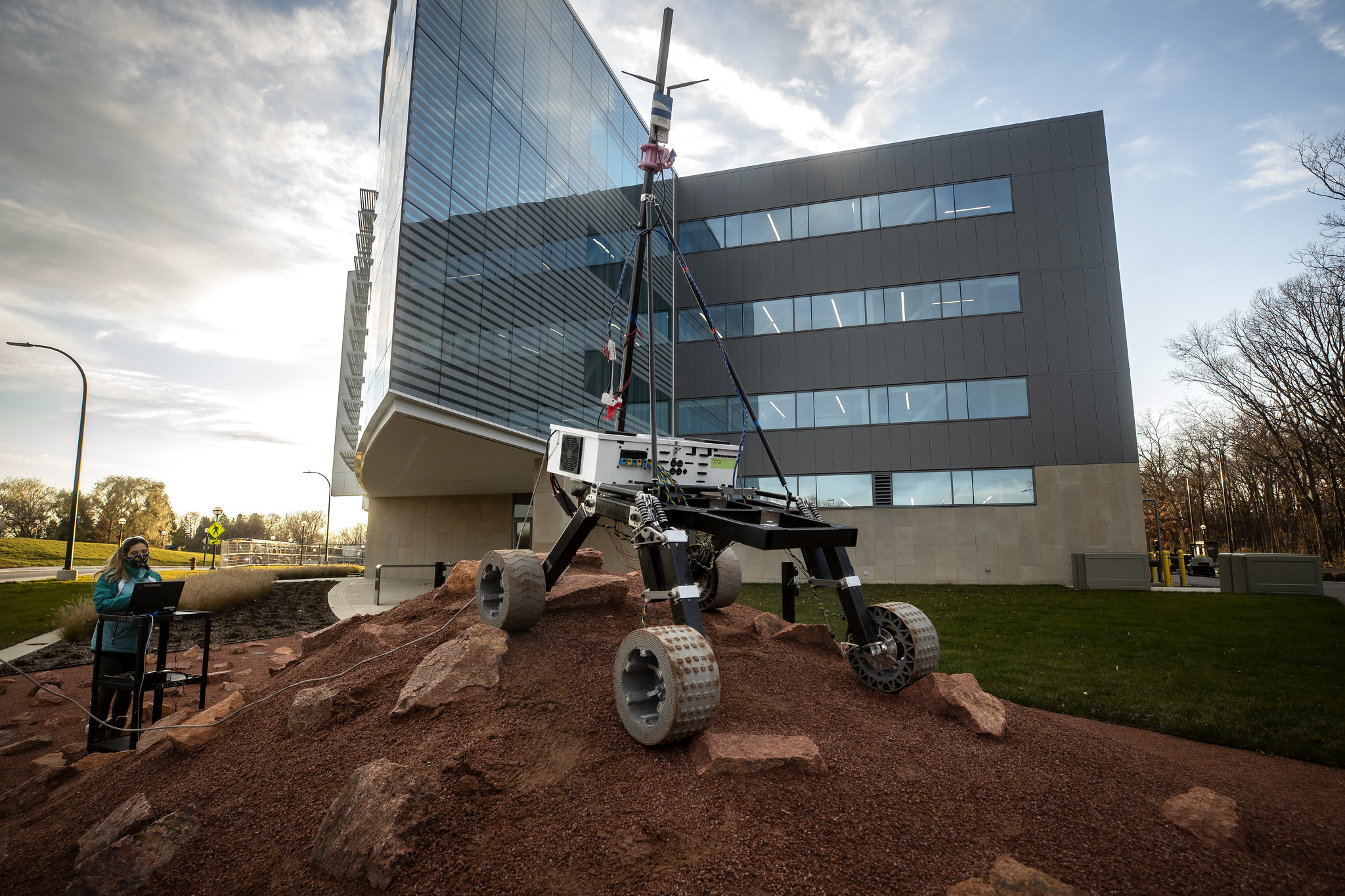 A photograph of a Mars Rover outside of the Ford Robotics Building.