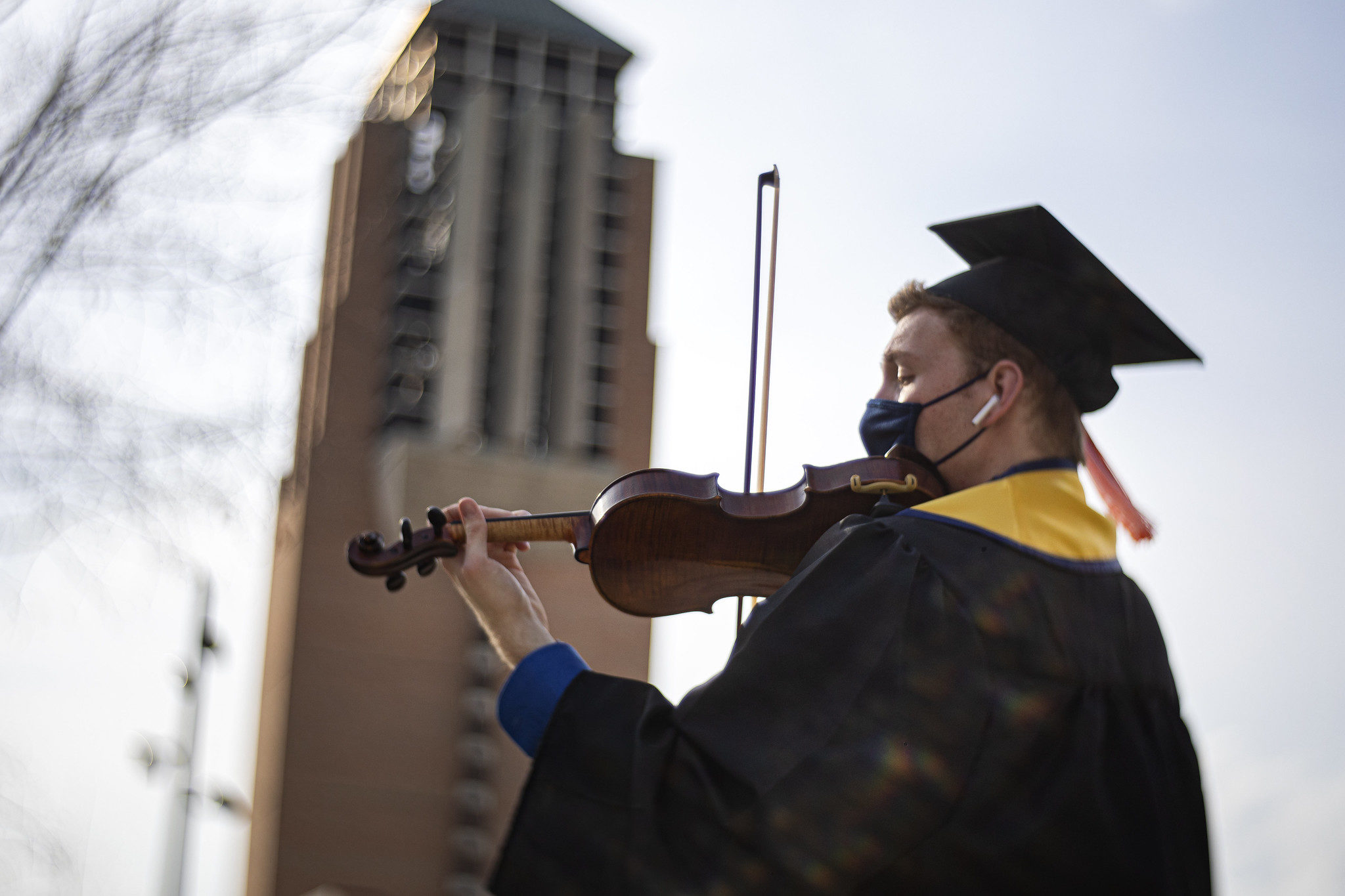 A photograph of a student playing violin on the Grove.