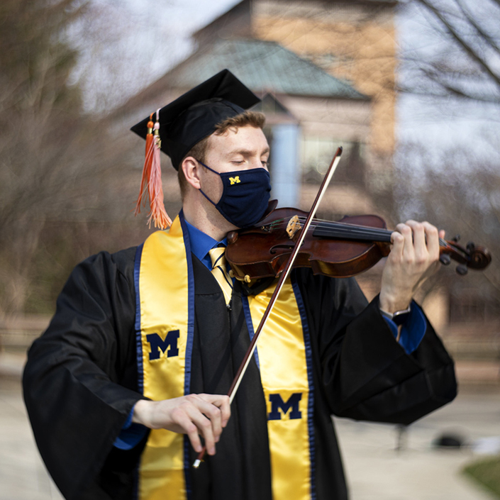Matthew Lamb plays the violin in grad cap and gown on North Campus