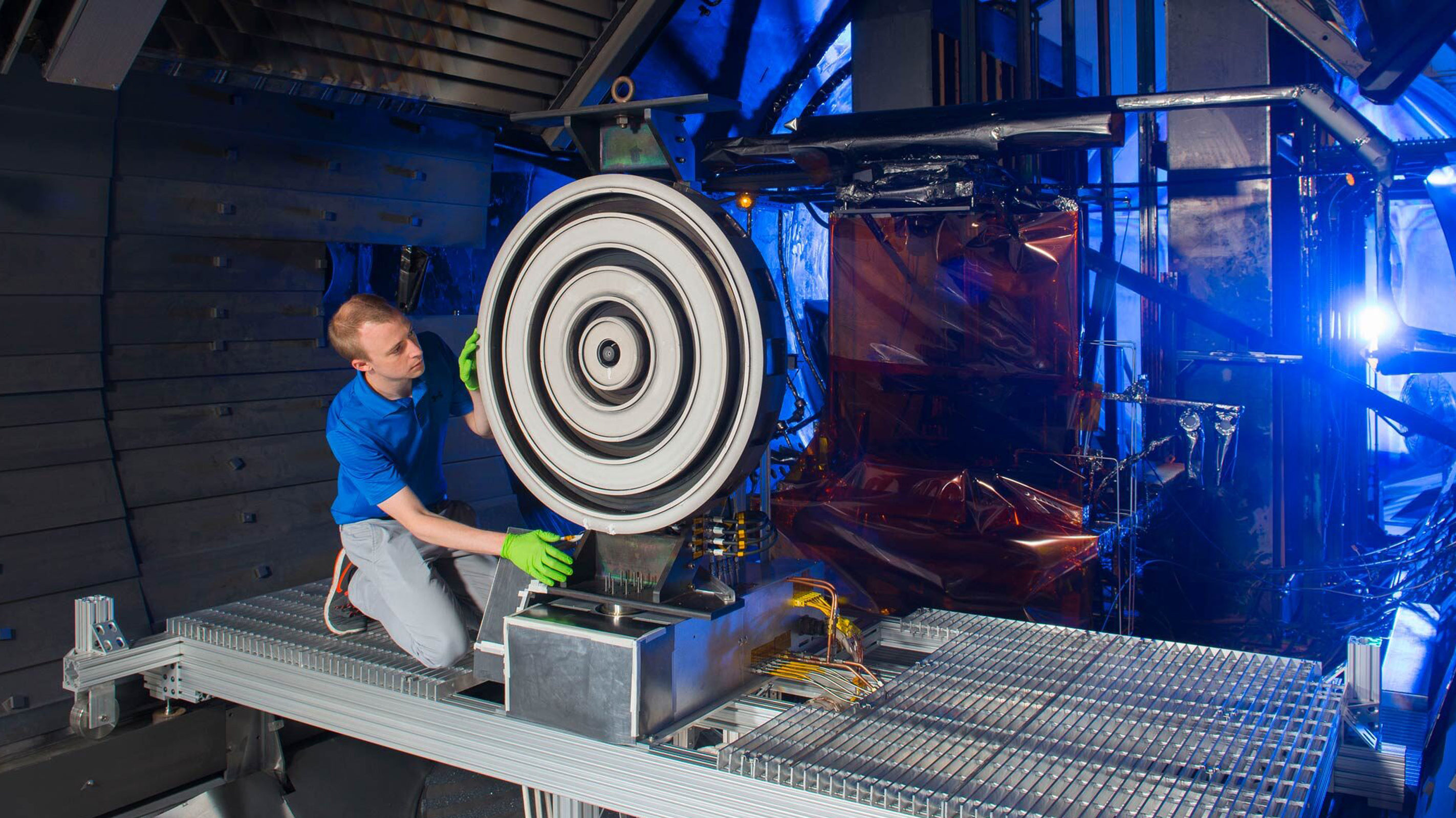 Scott Hall, former doctoral student in aerospace engineering at the University of Michigan, adjusts the record-setting X3 thruster at NASA Glenn Research Center in 2017.