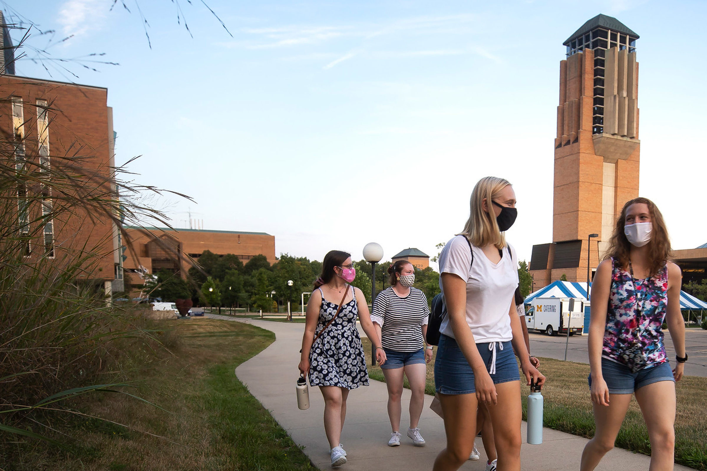 Four women walking in the Grove on campus