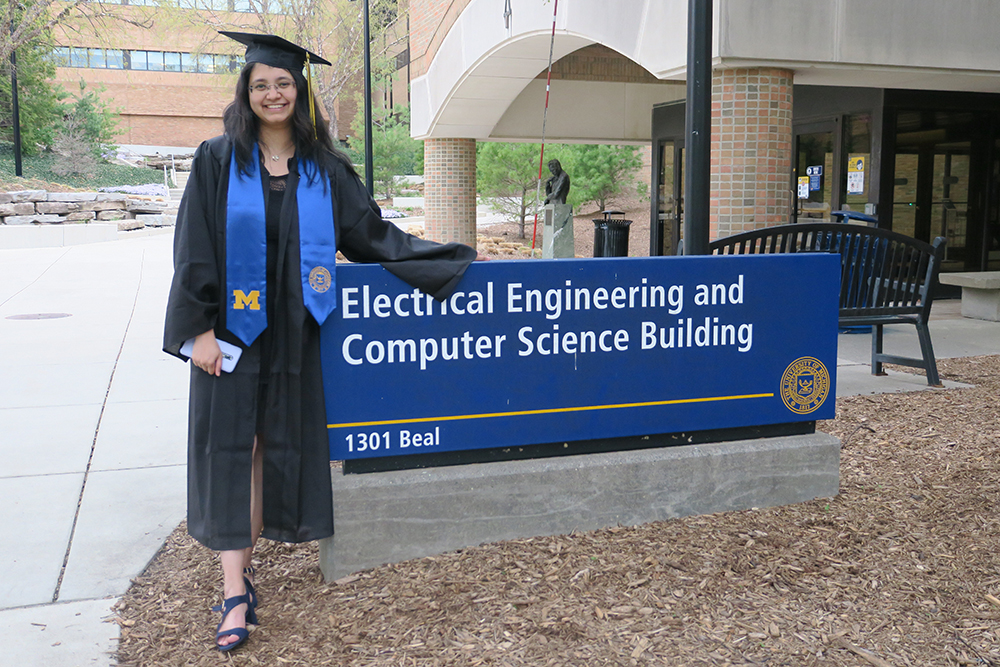 Rucha stands in grad cap and gown next to the EECS building sign